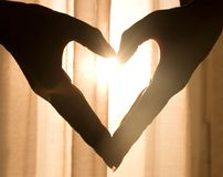 Beautiful heart made from hands, with light shining through stock images