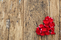 Beautiful heart of red rose petals on wooden background Royalty Free Stock Photo
