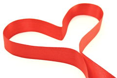 Beautiful heart from red satin ribbon. On a white background Stock Image