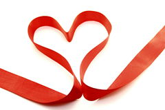 Beautiful heart from red satin ribbon. On a white background Stock Photos