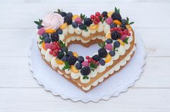 Beautiful heart shaped cake for Valentine`s day on white background. Beautiful heart shaped cake with fresh berries for Valentine`s day on white wooden royalty free stock photos