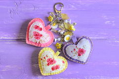 Beautiful hearts and flowers keyring. Handmade felt and fabric keyring or bag charm isolated on lilac wooden background Stock Photos