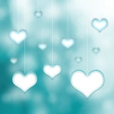 Beautiful hearts hang on cyan color bokeh background Stock Images
