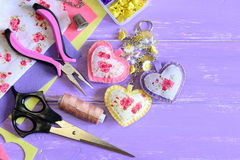 Beautiful hearts keyring. Hand felt and fabric keyring or bag charm. Organizer with plastic flowers, scissors, pliers, felt. Felt crafts. Felt sewing. Sewing Stock Photo