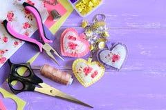 Beautiful hearts keyring. Hand felt and fabric keyring or bag charm. Organizer with plastic flowers, scissors, pliers, felt Stock Photo