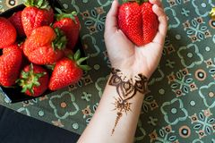 Female hand with arabic or indian mehendi and giant strawberry. Beauty and fashion concept. traditional patterns royalty free stock photography