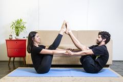Beautiful hetero caucasian couple in black clothes on blue yogamat doing buddy boat pose