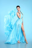 Beautiful High Fashion model in blue blowing chiffon dress. Glam. Our stunning Woman in long flying silk fabric waving on wind evening dress Royalty Free Stock Photography