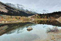 Beautiful high mountains of the Canadian Rockies reflecting in an alpine lake along the Icefields Parkway between Banff and Jasper. In the fall royalty free stock photos