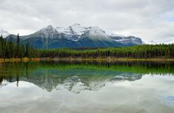 Beautiful high mountains of the Canadian Rockies reflecting in an alpine lake along the Icefields Parkway between Banff and Jasper. In the fall stock image