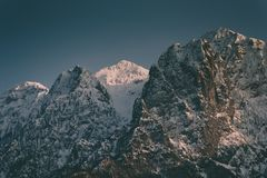 Beautiful high rocky mountains with a snowy mountain in between stock images