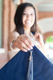 Beautiful high school graduate holding out graduation hat. Royalty Free Stock Photo