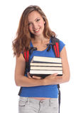 Beautiful high school teenage girl in education. Beautiful high school teenager girl holding education books, with long brown hair wearing blue t-shirt and red Royalty Free Stock Images