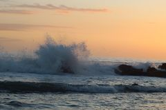 The beautiful high waves in the ocean in Marina di Massa in Italy with a view to the beach with nice colours of the sunset. Beautiful high waves ocean marina stock photography