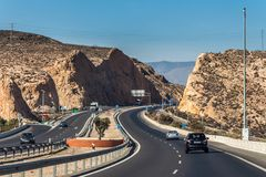 A highway among the yellow mountains is near Almeria in Spain. A beautiful highway with road signs and cars among the yellow mountains with small green plants is Stock Photography