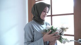 Beautiful hijab woman holding flowers with a happy smile expression while stroking the window curtain