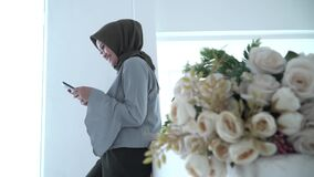 Beautiful hijab woman is typing a message on her phone. While standing near her window