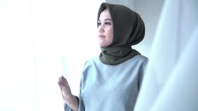 Beautiful hijab woman was holding and stroking the window curtain with a smile expression as if she was missing someone