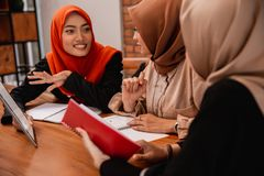 Beautiful hijab woman smiling when chatting with her university friends royalty free stock photography