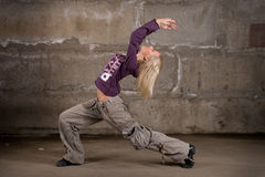Beautiful hip-hop girl dancing over brick wall Stock Images