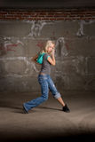 Beautiful hip hop girl dancing over brick wall Royalty Free Stock Photography