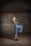 Beautiful hip hop girl dancing over brick wall Stock Images