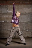 Beautiful hip hop girl dancing over grey brick wal Stock Photo