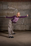 Beautiful hip hop girl dancing over grey brick wal Stock Images