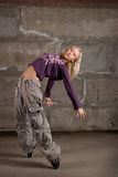 Beautiful hip hop girl dancing over grey wall Royalty Free Stock Photo