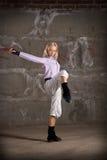 Beautiful hip hop girl dancing over grey wall Royalty Free Stock Photo