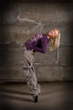 Beautiful hip hop girl dancing over grey wall Stock Images
