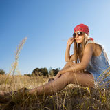 Beautiful hippie looking girl sitting on a meadow - morning  outdoors shot Royalty Free Stock Image