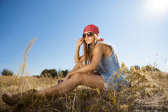 Beautiful hippie looking girl sitting on a meadow - morning shot Stock Photo