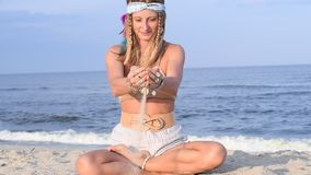Beautiful hippie woman with accessories is pouring sand through fingers at the beach in slow motion