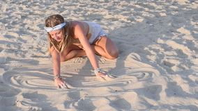Beautiful hippie woman with bracelets and rings is touching sand on the beach