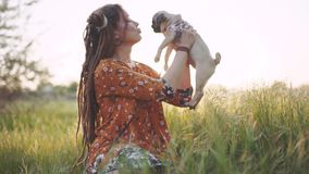 Beautiful hippie woman with dreadlocks in green grass with her puppy of pug-dog at sunset having good time outdoors