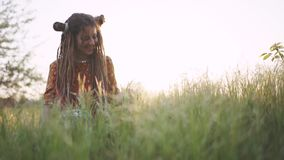 Beautiful hippie woman with dreadlocks in green grass at sunset having good time outdoors