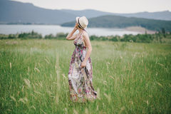 Beautiful hippie woman posing on a green field with mountains on the background. Stock Image