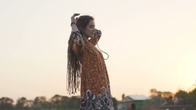 Beautiful hippie woman throws up her dreadlocks at sunset . 120fps slow motion