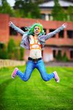 Beautiful hipster alternative young woman with green hair jump Stock Image