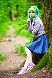 Beautiful hipster alternative young woman with green hair in park Stock Image