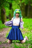 Beautiful hipster alternative young woman with green hair in park Royalty Free Stock Images