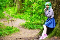 Beautiful hipster alternative young woman with green hair in park Stock Photography