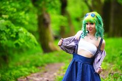 Beautiful hipster alternative young woman with green hair in park Royalty Free Stock Image