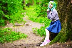 Beautiful hipster alternative young woman with green hair in park Royalty Free Stock Photography