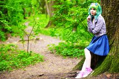 Beautiful hipster alternative young woman with green hair in park Stock Photo