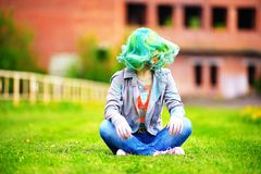 Beautiful hipster alternative young woman with green hair sits on grass Royalty Free Stock Photos