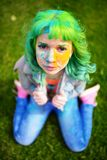 Beautiful hipster alternative young woman with green hair sits on grass Stock Photos