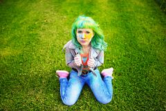 Beautiful hipster alternative young woman with green hair sits on grass Royalty Free Stock Photography
