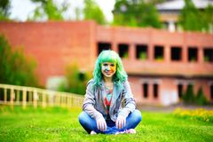 Beautiful hipster alternative young woman with green hair sits on grass Stock Images